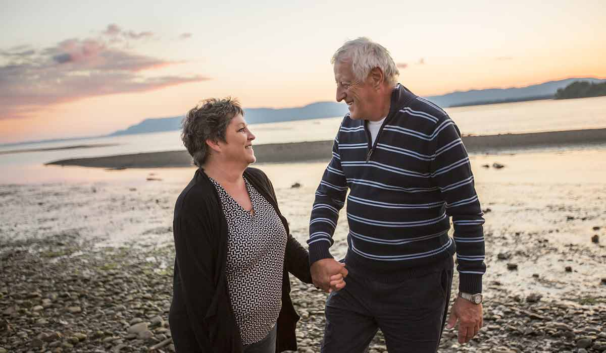 Over 50s couple holding hands on beach