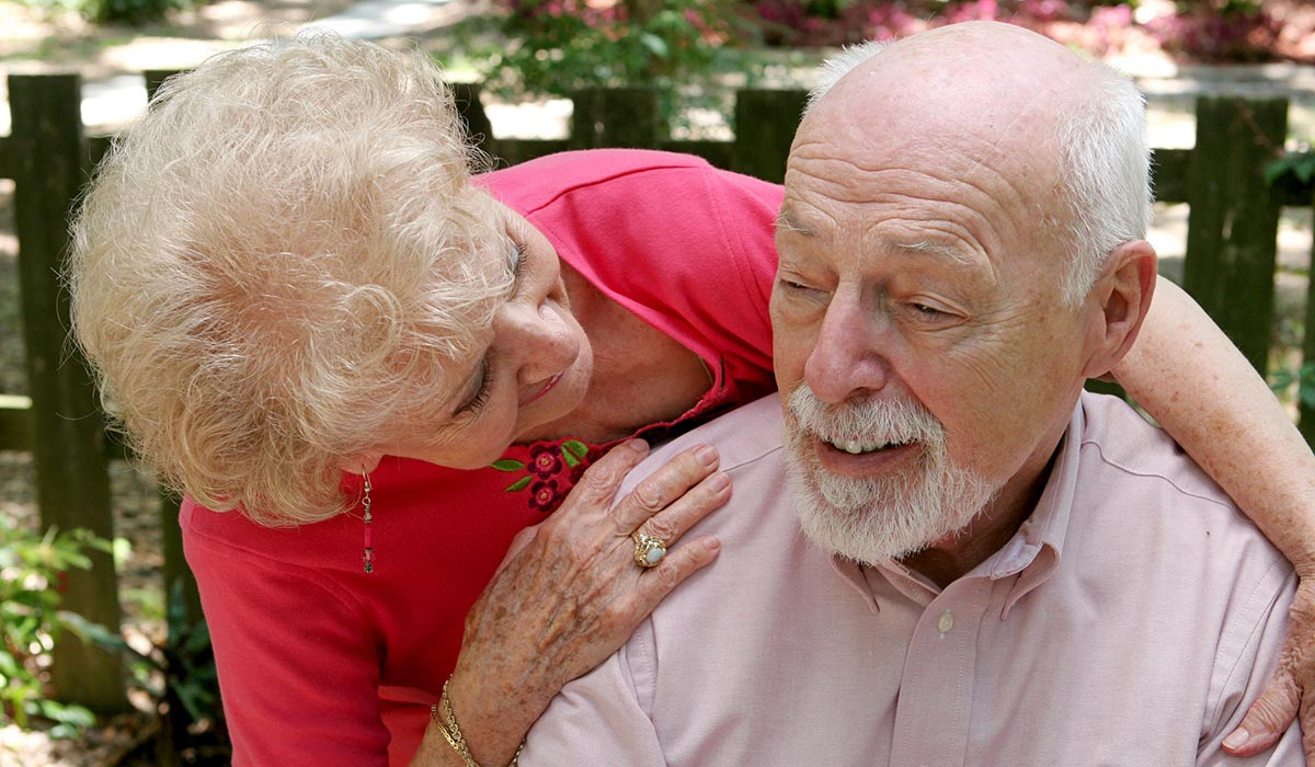 elderly couple looking and smiling at each other